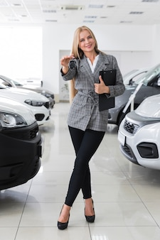 Happy woman holding car keys long shot