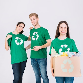 Happy woman holding cardboard box with recycle items in front of her friends
