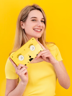 Happy woman holding cassette