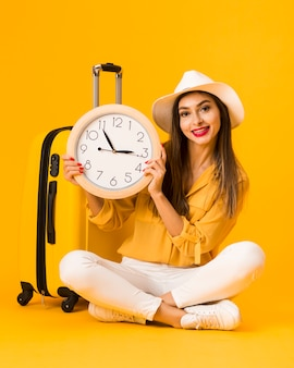 Happy woman holding clock next to luggage