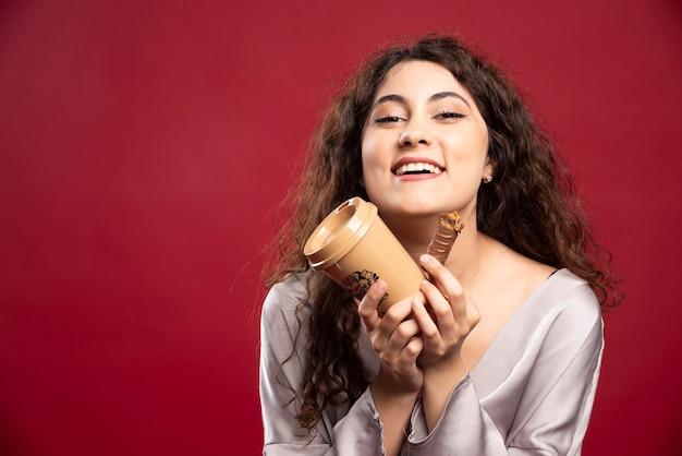 Счастливая женщина, держащая кофе и шоколад.