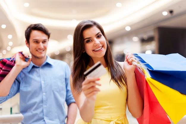 Счастливая женщина, держащая кредитную карту и хозяйственные сумки