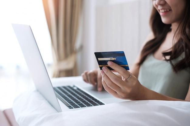 Счастливая женщина держа кредитную карточку и используя компьтер-книжку компьютера для онлайн покупок пока делающ заказы на кровати в утре дома.