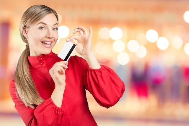 クレジットカードを保持している幸せな女。ショッピングのコンセプト