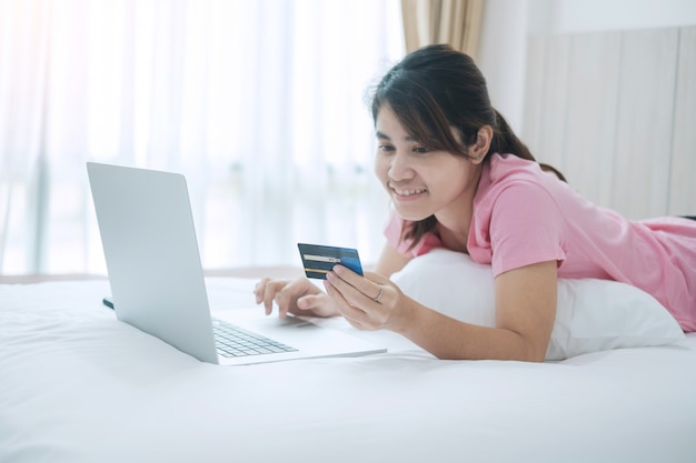 Happy woman holding credit card and using computer laptop for online shopping while making orders on bed in morning at home.