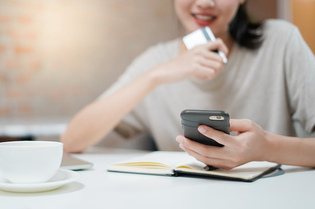 Happy woman holding credit card and using smartphone to shop online