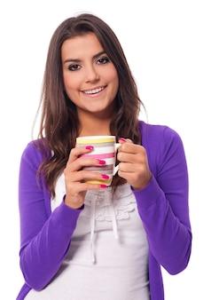 一杯のコーヒーを保持している幸せな女性