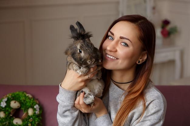イースターのウサギを押しながらイースターエッグの壁と春の花輪のカメラに笑顔幸せな女