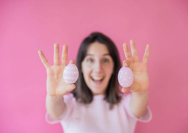 Счастливая женщина держит пасхальные яйца