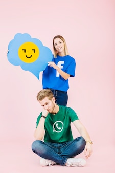 Happy woman holding emoji speech bubble behind upset man