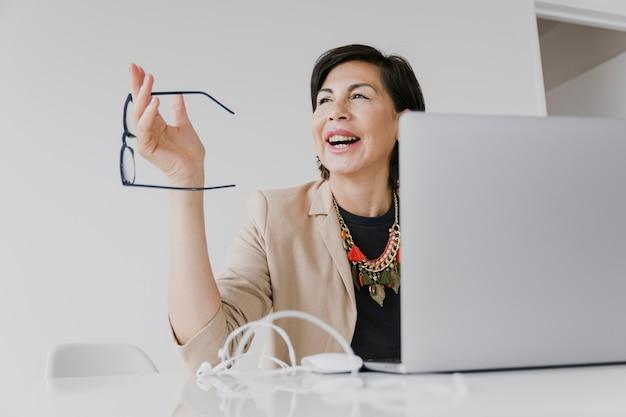 Happy woman holding eyeglasses medium shot