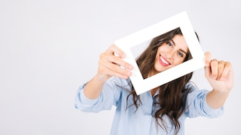 Happy woman holding frame in front of face