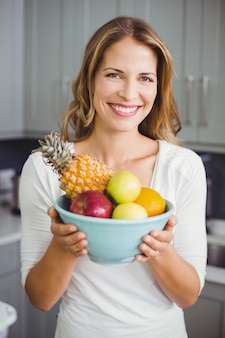 Happy woman holding a fruit bowl