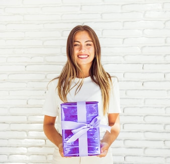 Happy woman holding gift box against brick wall