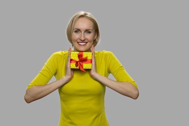 양손으로 선물 상자를 들고 행복 한 여자입니다. 회색 배경에 손에 작은 선물 상자 꽤 웃는 여자.