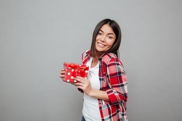 Счастливая женщина держит подарок над серой стеной
