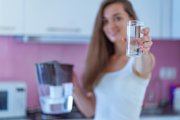Happy woman holding glass of purified water in the kitchen at home