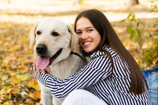 Happy woman holding her labrador