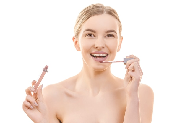 The happy woman holding a lip gloss on the white background