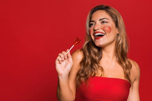 Happy woman holding lollipop