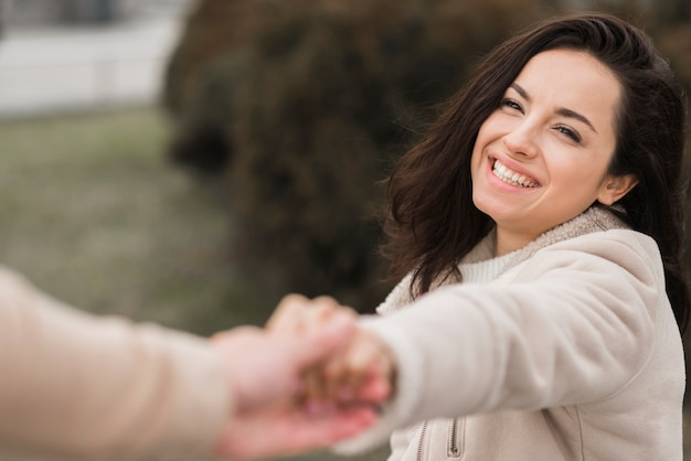 Happy woman holding man's hand outdoors