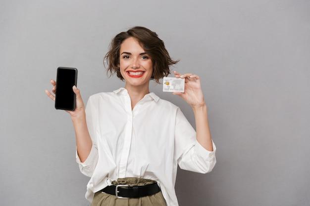 携帯電話とクレジットカードを保持している幸せな女性、灰色の壁に隔離