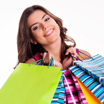 Happy woman holding multi colored shopping bags
