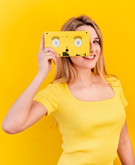 Happy woman holding old cassette