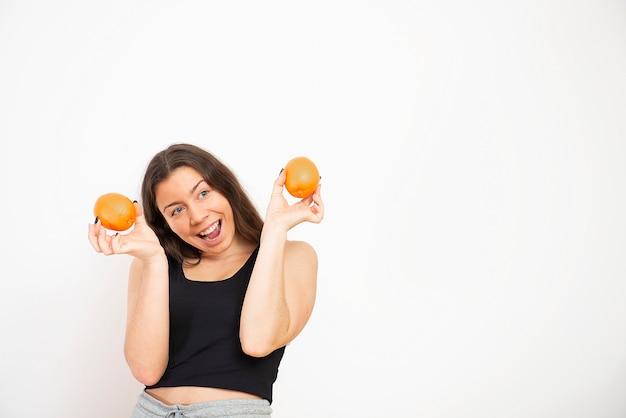 Счастливая женщина, держа в руке апельсиновый фрукт. концепция здорового образа жизни, диеты и питания.