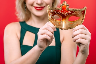 Happy woman holding orange mask in hands