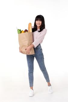 Счастливая женщина, держащая бумажный пакет, полный свежих овощей и багета