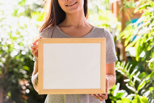 Happy woman holding photo frame between plants