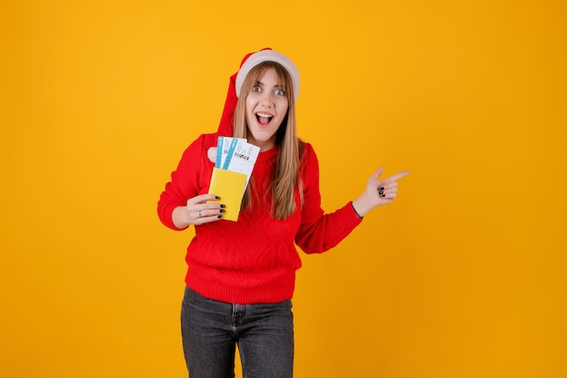 Happy woman holding plane tickets and passport wearing santa hat