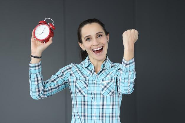 빨간색 알람 시계를 들고 행복 한 여자입니다. 시간 개념에 대한 비즈니스 프로젝트 제공
