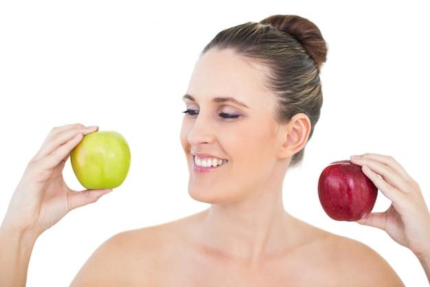赤と緑のリンゴを持っている幸せな女性