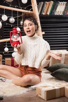 Donna felice con in mano una lampada di natale rossa