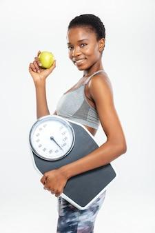 Счастливая женщина, держащая весы и яблоко, изолированные на белой стене