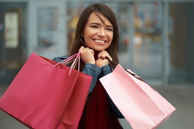 쇼핑 가방을 들고 쇼핑몰 근처에 웃 고 행복 한 여자