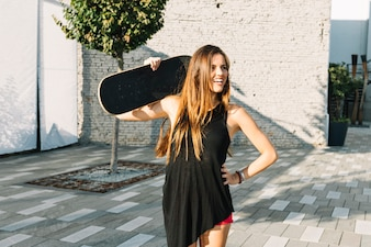 Happy woman holding skateboard at outdoors
