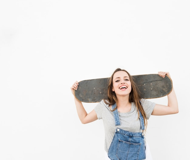 Happy woman holding skateboard on her shoulder against white backdrop