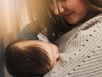 眠っている赤ちゃんを腕の中で保持している幸せな女