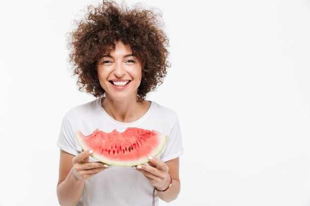 Happy woman holding slice of a watermelon