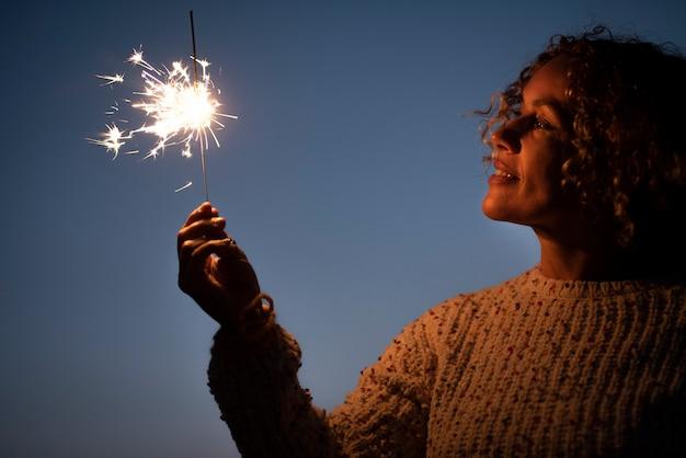 線香花火の光を保持し、空の背景で祝う幸せな女性