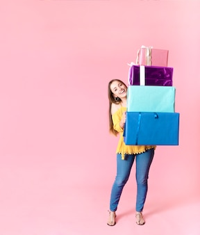 Happy woman holding stack of colorful gift boxes against pink backdrop
