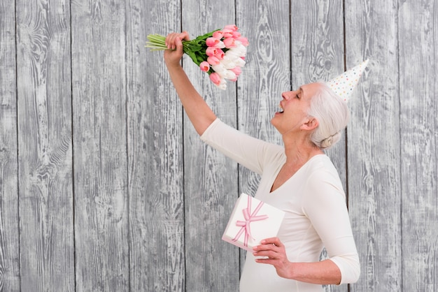Happy woman holding tulip flower bouquet and gift box in front of gray background
