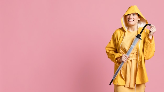 Happy woman holding an umbrella with copy space