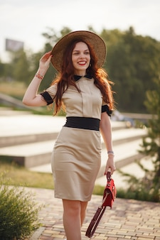 A happy woman, holding a wide hat, poses in a park in summer