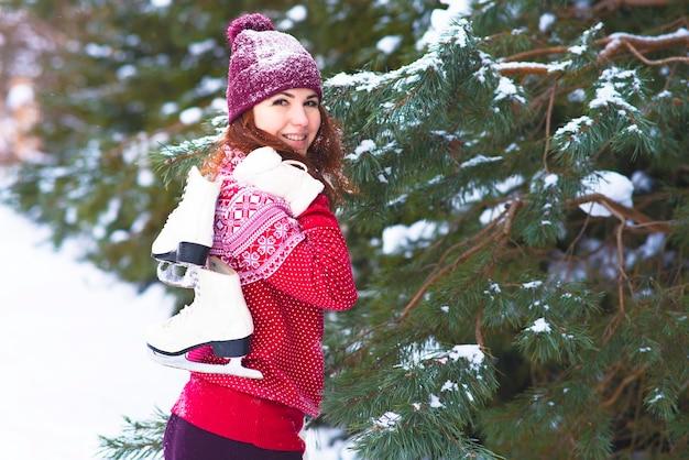 彼女の肩に冬のスケート靴を保持している幸せな女性。冬のアクティビティとスポーツ。