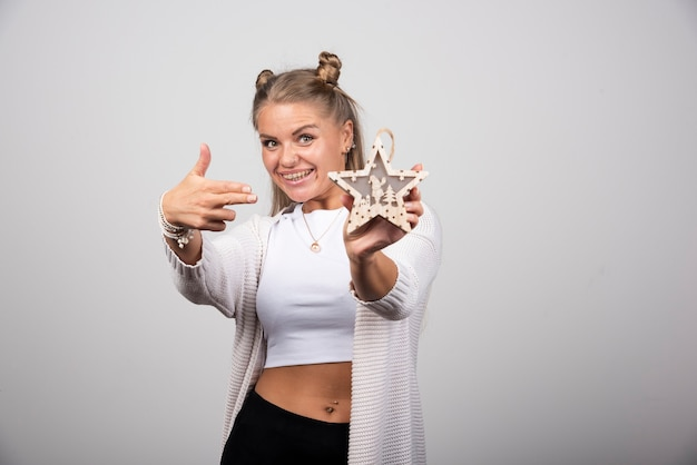 Happy woman holding wooden star and pointing at it.