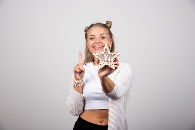 Happy woman holding wooden star and pointing upside.